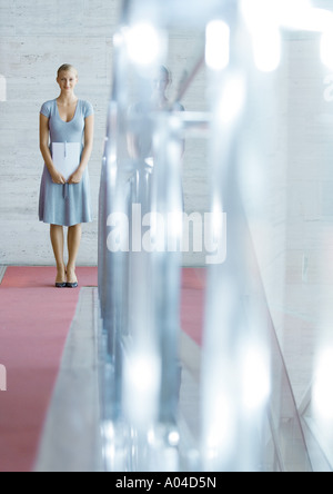 Young woman standing, holding papers,  in mid-distance - Stock Photo