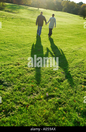 young couple walking on grass - Stock Photo