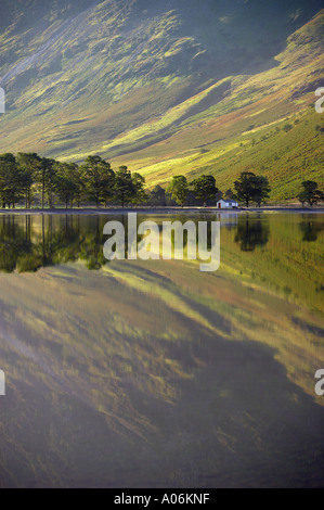 reflections on the shore of Buttermere at dawn Lakes District Cumbria England UK - Stockfoto