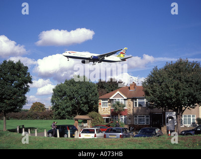 London Airport perimeter British Airways low flying passenger jet approaches runway above residential housing - Stock Photo