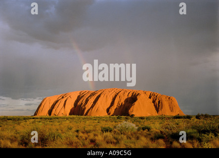 Rainbow over Ayers Rock Australia, Northern Territory - Stock Photo