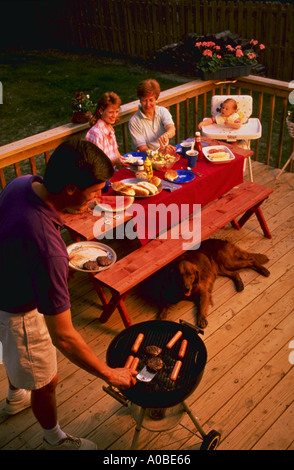 Three generations of family having cook out on back porch - Stock Photo