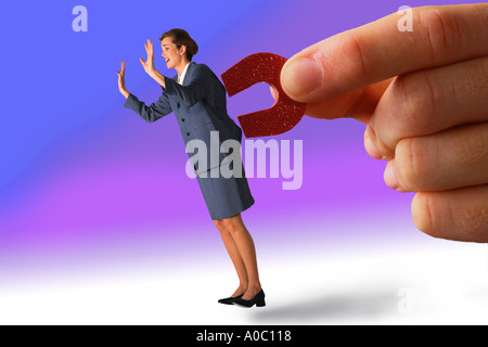 Businesswoman pulled by magnet - Stock Photo
