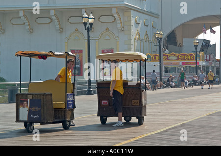 Two rickshaws  talking on the boardwalk Atlantic City NJ New Jersey USA - Stock Photo
