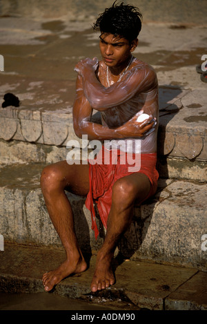 Indian young man washing in the sacred Ganges River Varanasi Uttar Pradesh India - Stockfoto