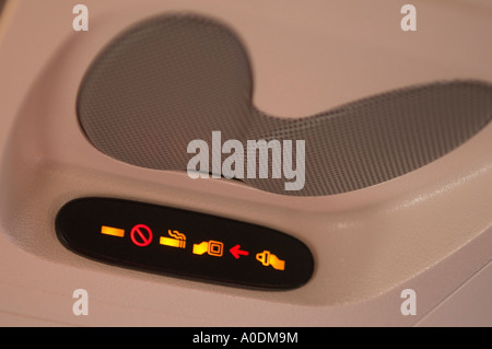 lighted signs and speakers overhead in passenger compartment of commercial airliner - Stock Photo
