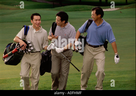 Three men carrying golf bags at a golf course - Stockfoto