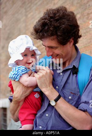 father carrying baby daughter, wearing cute sunhat - Stock Photo