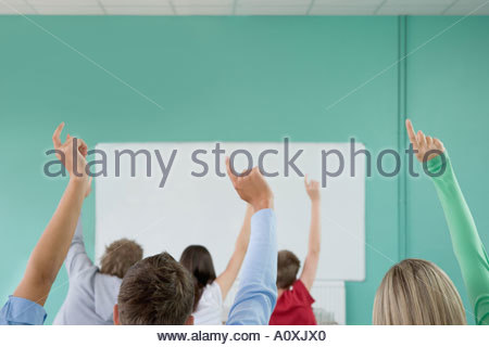 School students raising their hands - Stock Photo