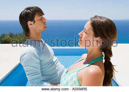 Couple by swimming pool - Stock Photo