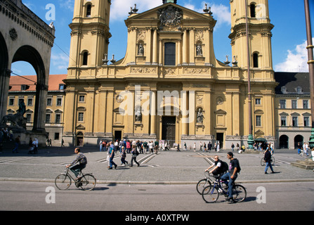 Cyclists passing the Theatinerkirche church Munich Bavaria Germany Europe - Stock Photo