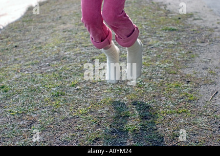 Girl playing with a skipping rope outdoors - Stockfoto