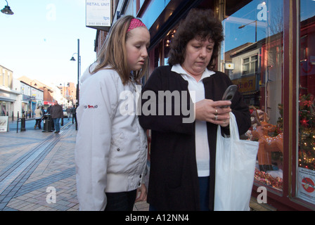 Mother and daughter using mobile phone in street England UK United Kingdom GB Great Britain EU European Union Europe - Stock Photo