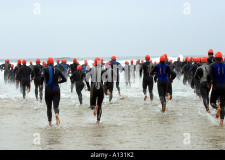 Competitors entering the sea at the start of the Perranporth Triathlon Cornwall UK - Stock Photo