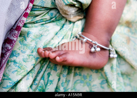 Indian babies bare foot against mothers green sari - Stock Photo