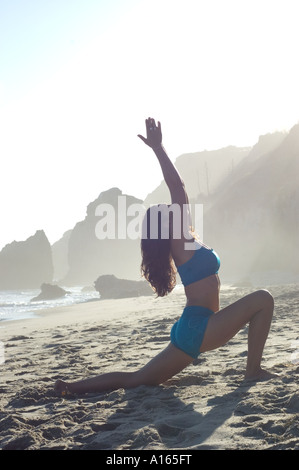Young woman practicing yoga on beach - Stock Photo