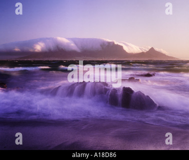 Table mountain at sunset covered by table cloth clouds Cape Town South Africa - Stock Photo