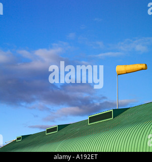 Windsock on top of a roof against blue sky - Stock Photo