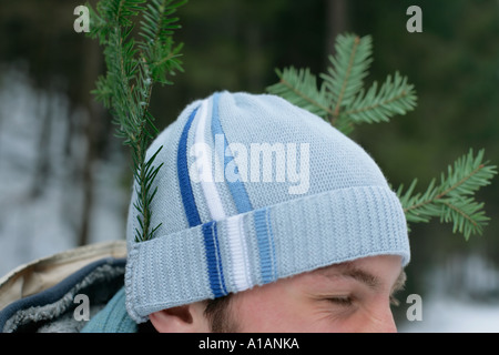 Man with pieces of tree in his hat - Stock Photo