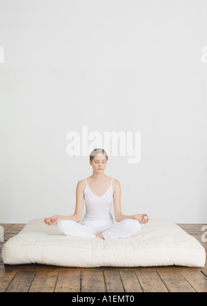 Young woman sitting in lotus position on futon mattress - Stock Photo