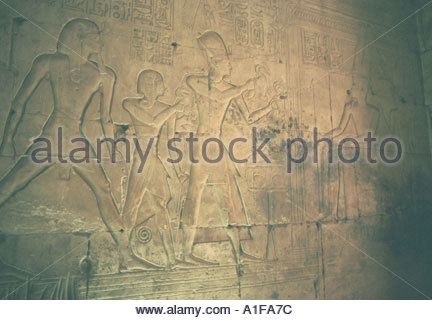 Ramasses 11 accompanied by a son makes an offering of ducks to the God Amen Re in wall relief in the Seti 1 Temple - Stock Photo