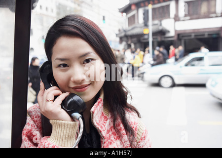 Portrait of a young woman using a telephone - Stock Photo