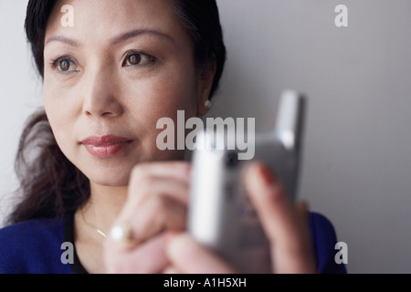 Close-up of a mature woman holding a mobile phone thinking - Stock Photo