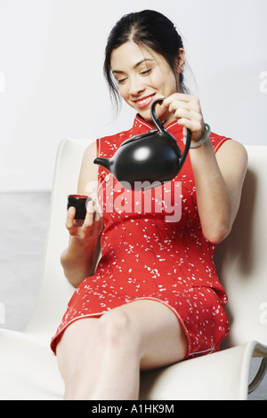 Close-up of a young woman holding a tea cup and a tea kettle - Stock Photo