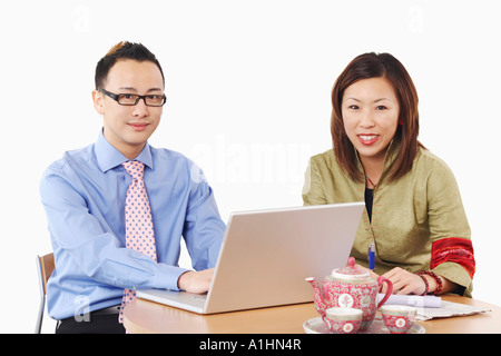 Portrait of a businessman and a businesswoman sitting in front of a laptop - Stock Photo