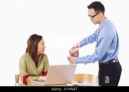 Side profile of a businessman pouring tea into a teacup in front of a businesswoman - Stock Photo