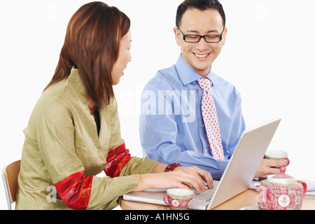 Side profile of a businesswoman and a businessman using a laptop - Stock Photo