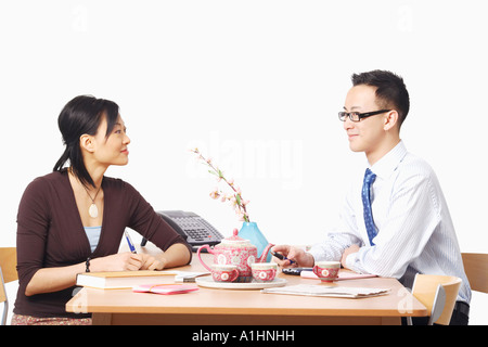 Businessman and a businesswoman sitting on chairs looking at each other - Stock Photo