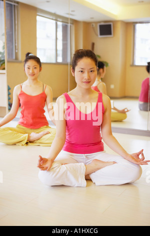 Portrait of a young woman sitting in the lotus position - Stock Photo