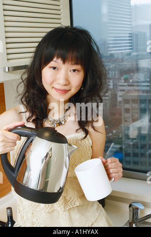 Portrait of a young woman holding a kettle and a mug - Stock Photo
