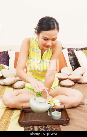 Close-up of a young woman pouring tea from a tea kettle into the cup - Stock Photo