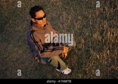 Kneeling Man Wearing Sunglasses - Stock Photo
