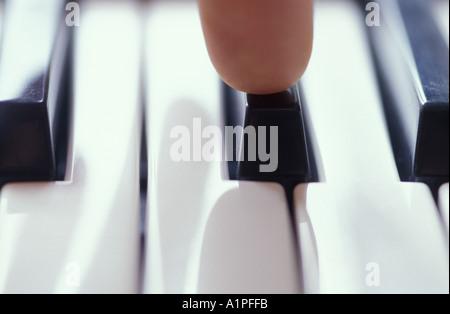 Human finger on piano keys, close-up - Stockfoto