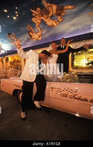 An Elvis impersonator and a newly wed couple in a Cadillac Convertible  Las Vegas Nevada USA - Stock Photo