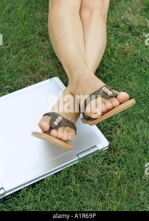 Woman lying in grass, legs resting on laptop computer, low section - Stockfoto