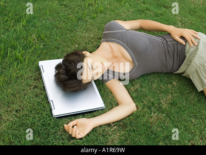 Woman lying in grass, head resting on laptop computer - Stockfoto