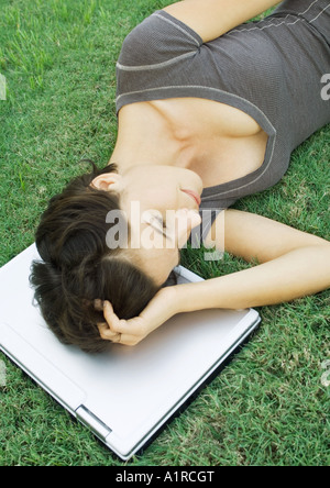 Woman lying in grass with head on laptop - Stockfoto