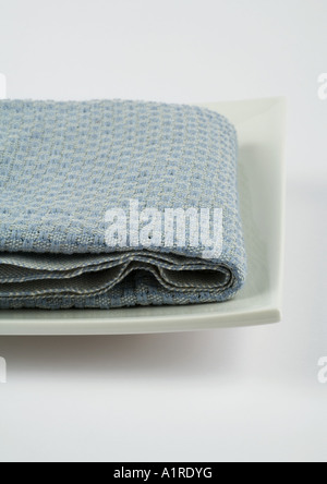 Towel folded on square dish - Stock Photo