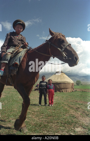 Young boy on a horse in front of their familys yurt, near Lake Issyk Kul, Kyrgyzstan - Stock Photo