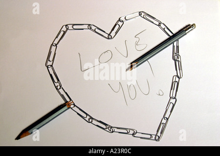 heart made out of paper clips with message Love You and broken pencil signifying an arrow - Stockfoto