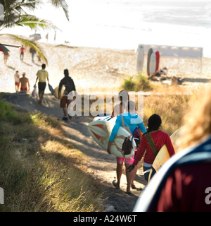 Surfers carrying boards to beach. No model release required back views distance and movement make any features unrecognizable - Stock Photo