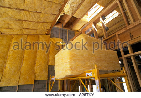R38 Fiberglass Insulation being installed roof in new loft style home under construction - Stock Photo
