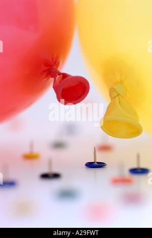 Two balloons huddled together and surrounded by drawing pins - Stock Photo