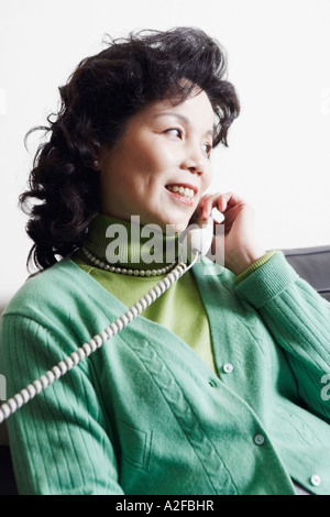 Close-up of a businesswoman using a telephone smiling - Stock Photo