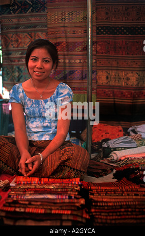 Lao textile vendor seated at her stall among footloom woven fabrics in the Hmong market on Sisavangvong Luang Prabang - Stock Photo
