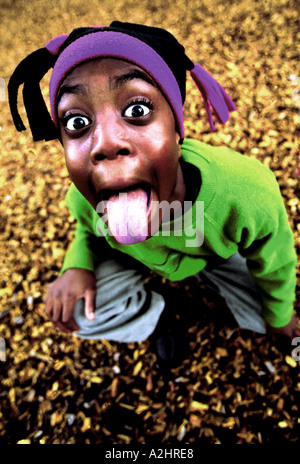 Negro boy age 8-10 pulling tongues into camera.The Image was shot from slightly above. - Stock Photo